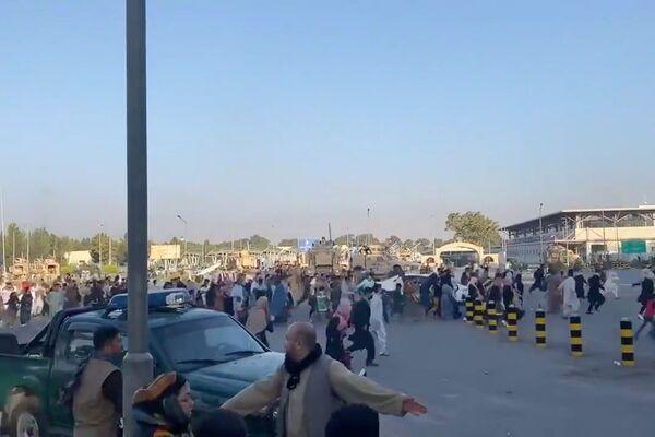 Tłum biegnie do terminalu lotniska w Kabulu po tym, jak bojownicy Talibanu* przejęli kontrolę nad pałacem prezydenckim. - Sputnik Polska