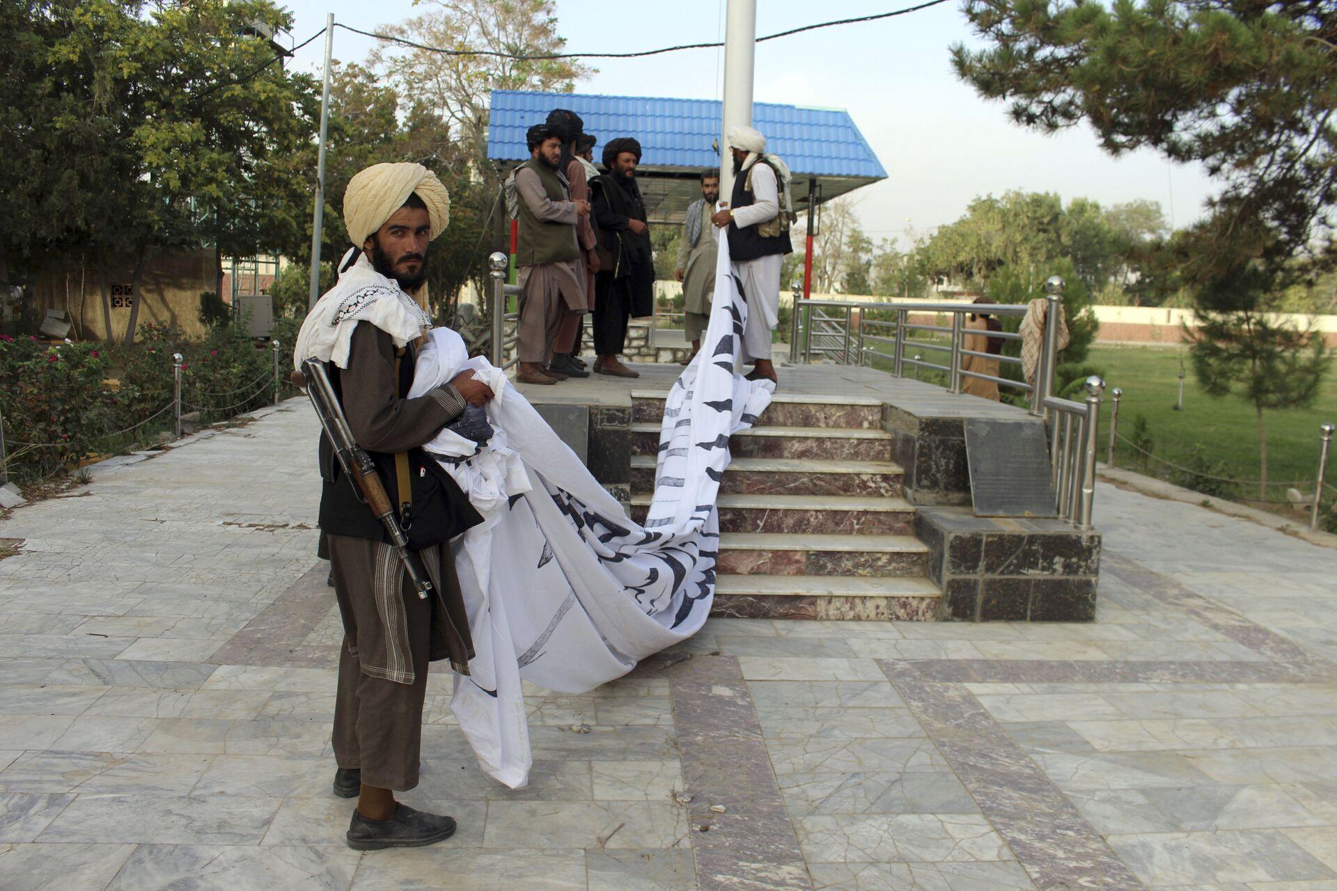 Bojownicy Taliban* wznoszą swoją flagę przed rezydencją gubernatora prowincji Ghazni, południowy wschód Afganistanu - Sputnik Polska, 1920, 16.08.2021