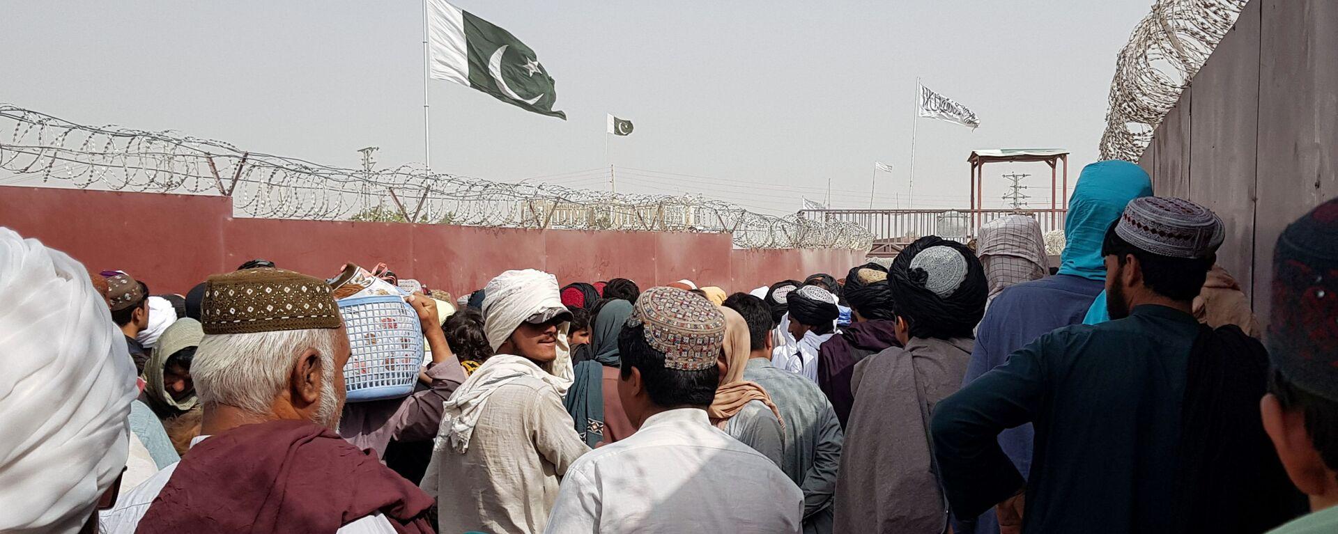 Flaga Pakistanu i flaga talibów widoczne na tylnym planie, kiedy ludzie kierują się do Afganistanu na przejściu granicznym Brama Przyjaźni w pakistańsko-afgańskim mieście granicznym Ćaman, Pakistan 15 sierpnia 2021 roku. - Sputnik Polska, 1920, 22.08.2021
