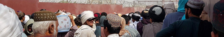 Flaga Pakistanu i flaga talibów widoczne na tylnym planie, kiedy ludzie kierują się do Afganistanu na przejściu granicznym Brama Przyjaźni w pakistańsko-afgańskim mieście granicznym Ćaman, Pakistan 15 sierpnia 2021 roku. - Sputnik Polska