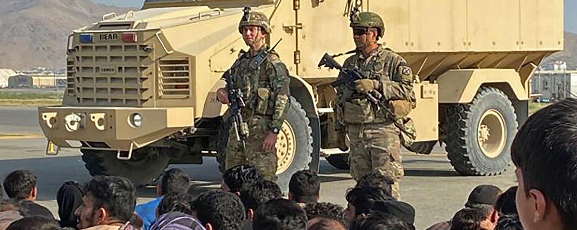 Afgańczycy tłoczą się na lotnisku, kiedy amerykańscy żołnierze stoją na straży w Kabulu 16 sierpnia 2021 roku. - Sputnik Polska, 1920, 17.08.2021