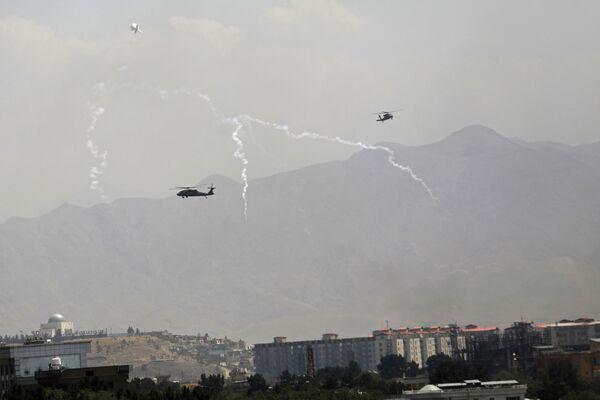 Wabiki przeciwrakietowe zostają uruchomione, gdy śmigłowce USA Black Hawk i balon sterowca przelatują nad miastem Kabul w Afganistanie, niedziela, 15 sierpnia 2021 roku - Sputnik Polska
