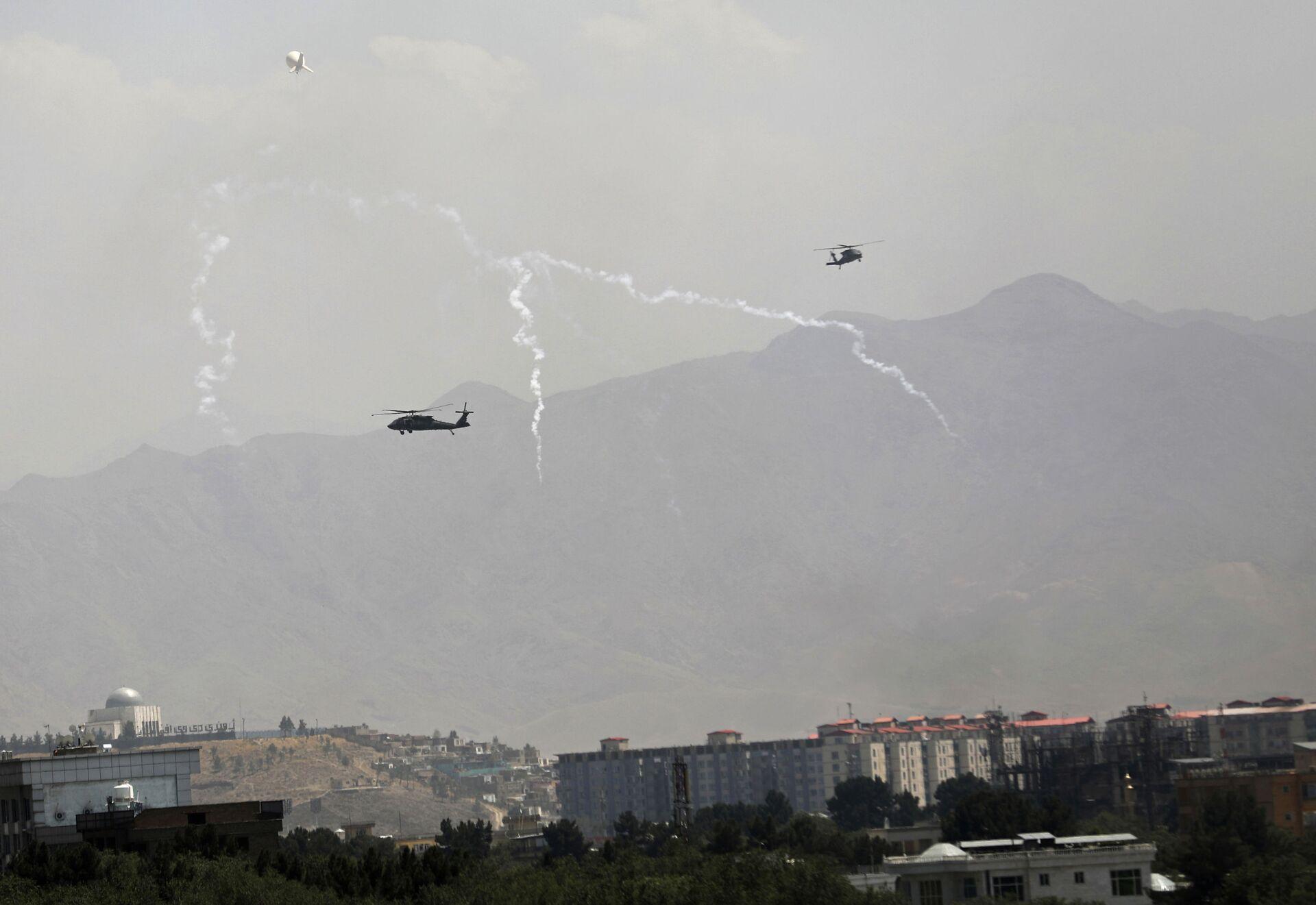 Wabiki przeciwrakietowe zostają uruchomione, gdy śmigłowce USA Black Hawk i balon sterowca przelatują nad miastem Kabul w Afganistanie, niedziela, 15 sierpnia 2021 roku - Sputnik Polska, 1920, 16.08.2021