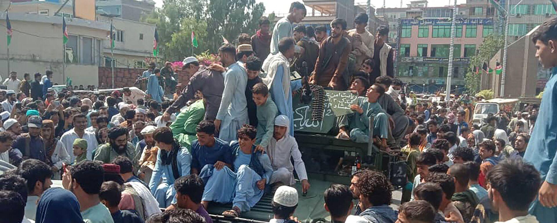 Bojownicy Talibana* i lokalni mieszkńcy siedzą w samochodzie Hammer Afgańskiej Armii Narodowej na ulicy w prowincji Dżalalabad 15 sierpnia 2021 roku. - Sputnik Polska, 1920, 17.08.2021