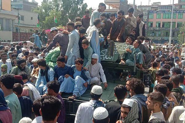 Bojownicy Talibanu* i lokalni mieszkańcy siedzą w samochodzie Hammer Afgańskiej Armii Narodowej na ulicy w prowincji Dżalalabad 15 sierpnia 2021 roku. - Sputnik Polska