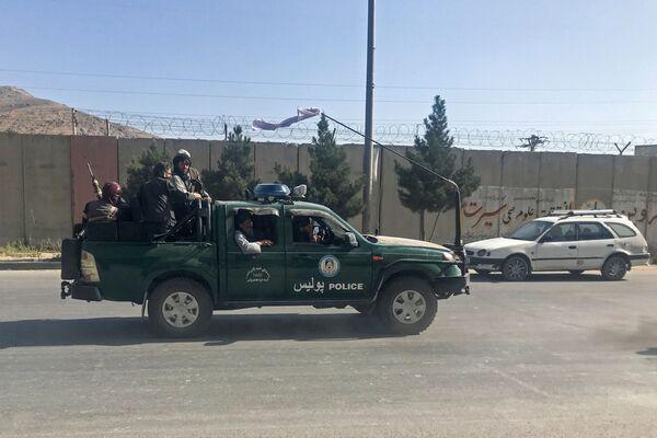 Bojownicy Talibanu* jadą radiowozem policyjnym w Kabulu, Afganistan, 16 sierpnia 2021 roku - Sputnik Polska