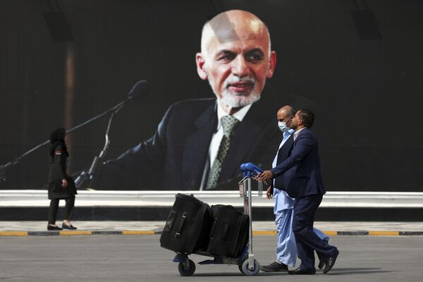 Pasażerowie idą do terminalu wylotów na międzynarodowym lotnisku im. Hamida Karzaja w Kabulu, Afganistan, 14 sierpnia 2021 roku. - Sputnik Polska