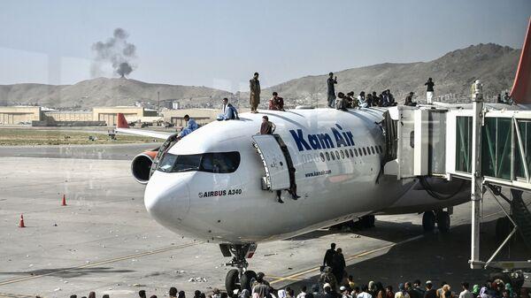 Афганцы забираются на самолет в аэропорту после вступления талибов в Кабул - Sputnik Polska