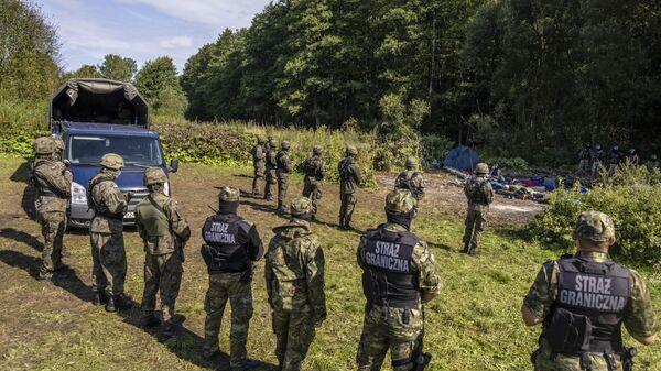 Польские и белорусские пограничники у импровизированного лагеря мигрантов на границе Белоруссии и Польши - Sputnik Polska