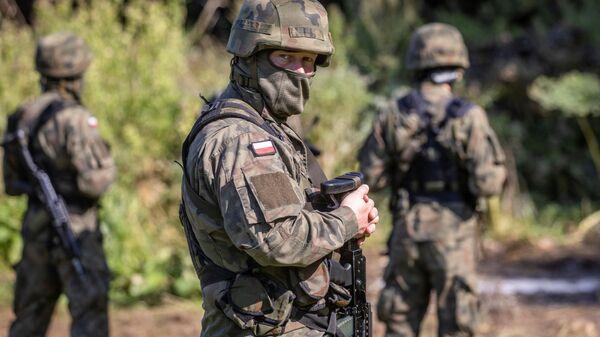 Вооруженный польский пограничник рядом с группой мигрантов в импровизированном лагере на границе между Беларусью и Польшей - Sputnik Polska