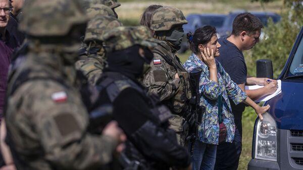 Польские и белорусские пограничники рядом с переводчиками и активистами, пытающимися общаться с группой мигрантов, предположительно из Афганистана, в селе Уснарз-Горный, Польша - Sputnik Polska