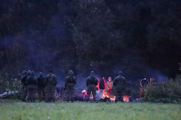 Polska Straż Graniczna pilnuje migrantów na granicy z Białorusią. Usnarz Górny, 18 sierpnia 2021 roku. - Sputnik Polska