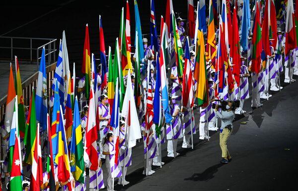 Podczas ceremonii otwarcia XVI letnich igrzysk paraolimpijskich wolontariusze trzymają flagi uczestniczących krajów  - Sputnik Polska
