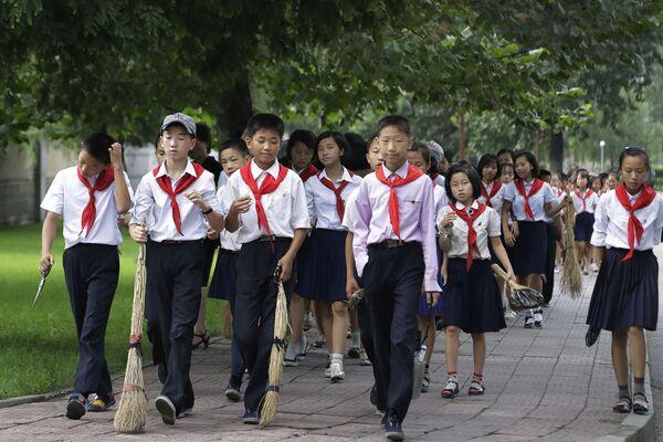 W Pjongjangu w Korei Północnej uczniowie niosą miotły, gdy idą do różnych miejsc publicznych, aby zamiatać i pielić trawę, aby utrzymać miasto w czystości. - Sputnik Polska