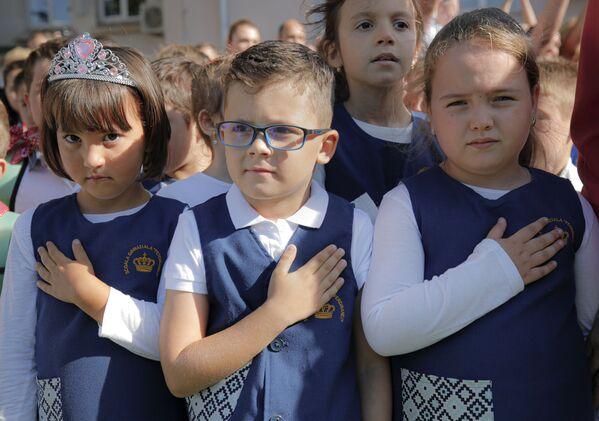 Dzieci trzymają ręce na piersiach podczas uroczystości rozpoczynających rok szkolny w szkole Ferdynanda I w Bukareszcie, Rumunia - Sputnik Polska