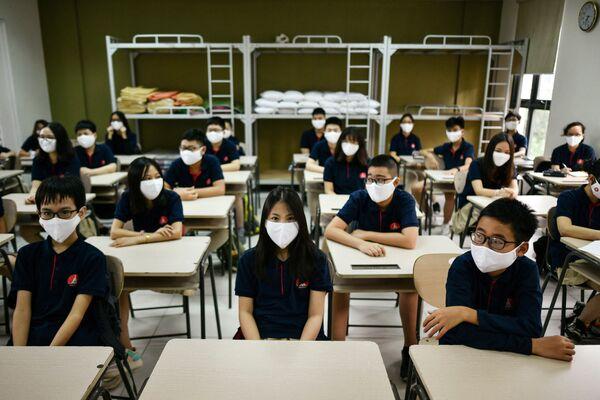 Uczniowie noszący maski na twarzach siedzą w klasie w szkole Marie Curie w Hanoi 4 maja 2020 r. - Sputnik Polska
