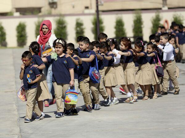 Uczniowie ustawiają się w kolejce, aby wejść do klasy w nowych mundurkach pierwszego dnia zajęć w Bagdadzie w Iraku  - Sputnik Polska