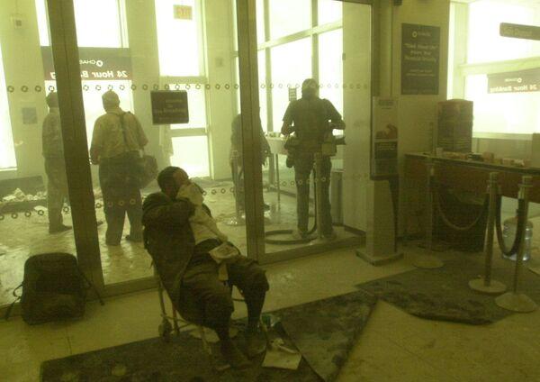 Ranny mężczyzna czeka na pomoc, podczas gdy inni szukają schronienia w banku w pobliżu wież World Trade Center 11 września 2001 r. w Nowym Jorku. Dwa samoloty uderzyły w każdy budynek i zawaliły się szczyty każdej wieży. - Sputnik Polska
