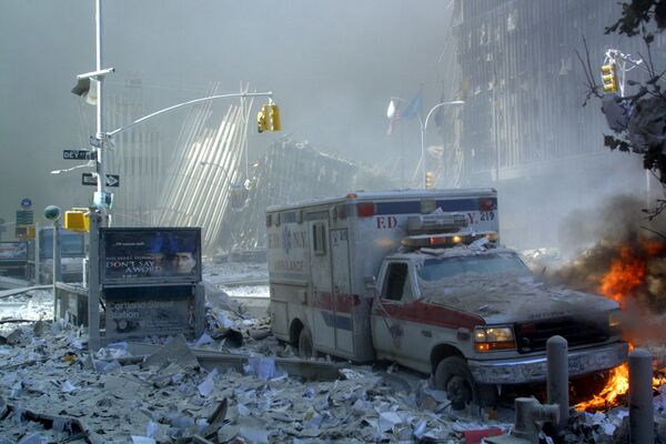 Karetka pogotowia, pokryta gruzami, płonie po zawaleniu się pierwszej wieży World Trade Center 11 września 2001 r. w Nowym Jorku.  - Sputnik Polska