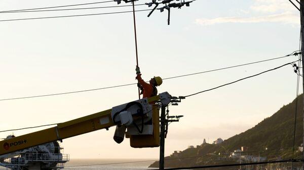 Рабочий электрической компании ремонтирует порванные линии электропередач и столбы в гавани после урагана Ларри, обрушившегося на Сент-Джонс, Ньюфаундленд, Канада - Sputnik Polska