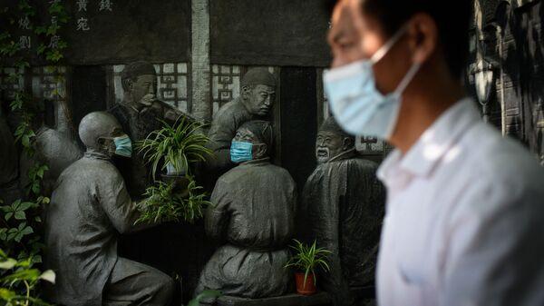 Мужчина проходит мимо скульптур в масках возле ресторана в Пекине - Sputnik Polska