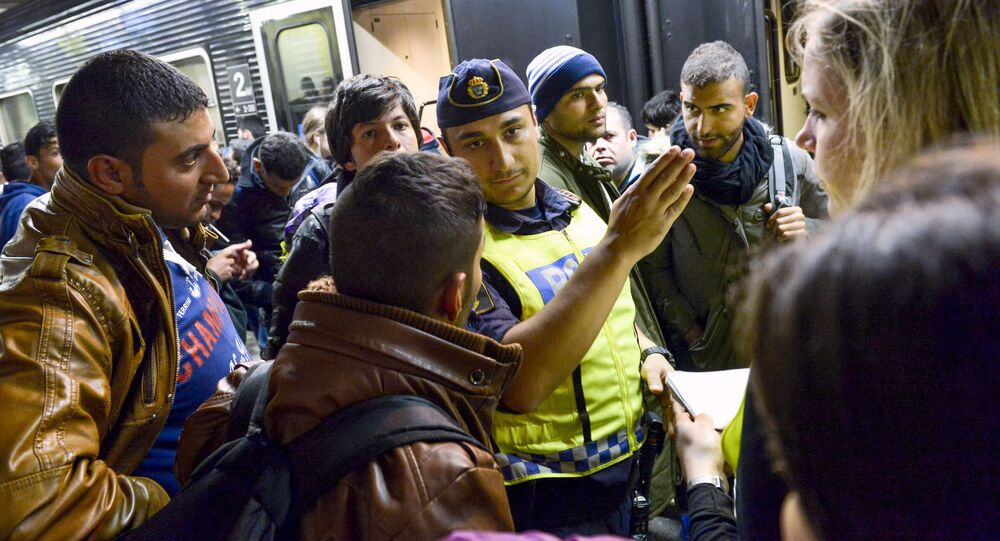 Szwecki policjant z imigrantami na dworcu kolejowym w Sztokholmie