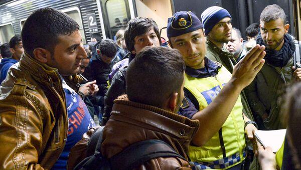 Szwecki policjant z imigrantami na dworcu kolejowym w Sztokholmie - Sputnik Polska