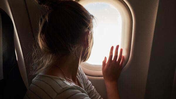 Kobieta wygląda przez okno w samolocie - Sputnik Polska