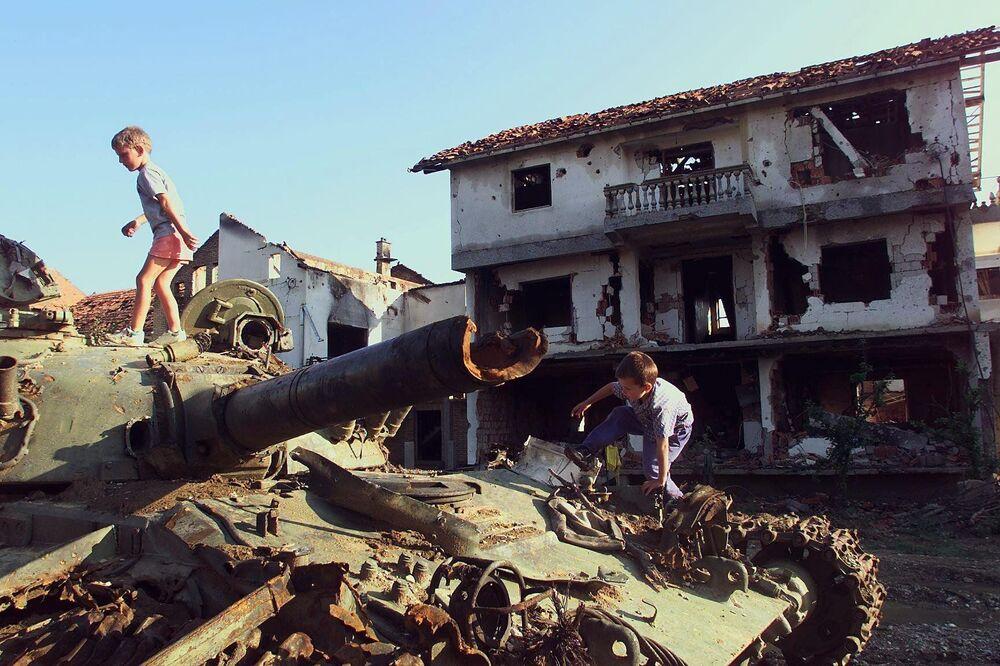 Dzieci bawią się na zniszczonym podczas bombardowań NATO serbskim czołgu w jugosłowiańskim mieście Klina, 1999 rok.