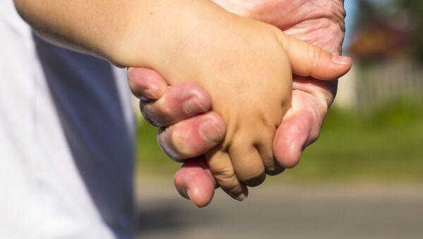 Dorosły prowadzi dziecko za rękę - Sputnik Polska