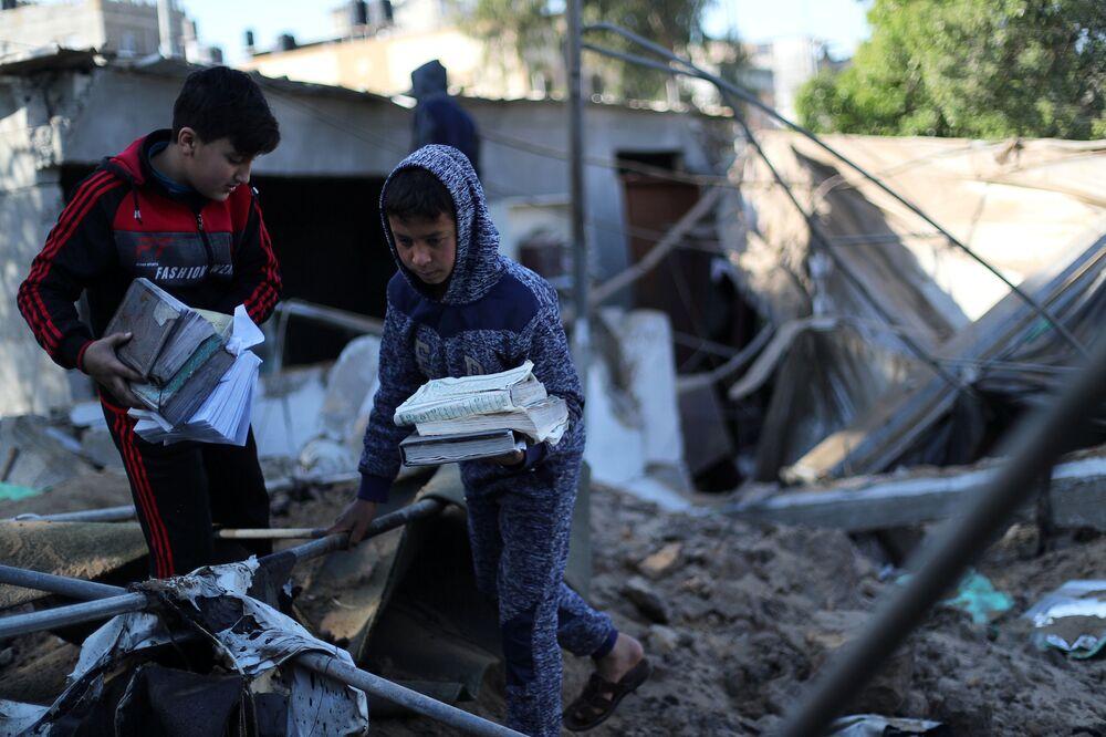 Palestyńskie dzieci zbierają strony Koranu, uszkodzonego podczas izraelskiego ataku na Strefę Gazy
