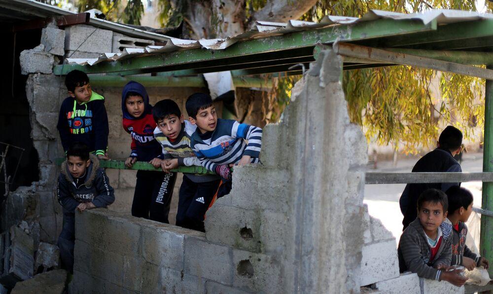Palestyńskie dzieci w zburzonych budynkach po izraelskim ataku na Strefę Gazy