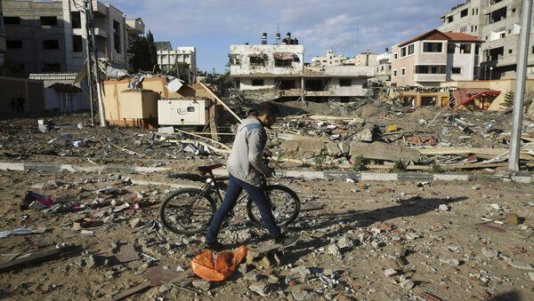 Mieszkaniec Strefy Gazy obok zburzonego budynku Hamasu po izraelskim ataku  - Sputnik Polska