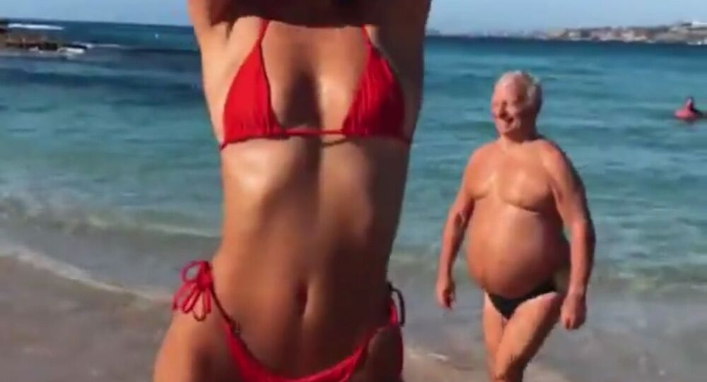 Kadr z sesji zdjęciowej na plaży modelki ze starszym mężczyzną na drugim planie