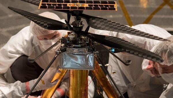 Członkowie zespołu NASA Mars Helicopter oglądają model miniaturowego śmigłowca przeznaczonego do lotów na Marsa - Sputnik Polska