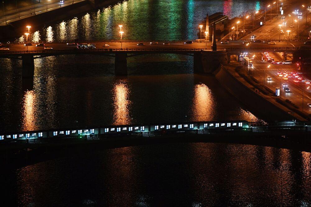 """Smolenskiy Metromost (na pierwszym planie) i Most Borodiński przez rzekę Moskwę po wyłączeniu oświetlenia w ramach akcji ekologicznej """"Godzina dla Ziemi""""."""