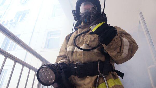 Funkcjonariusz Ministerstwa ds. Sytuacji Nadzwyczajnych w czasie ćwiczeń pożarowych - Sputnik Polska