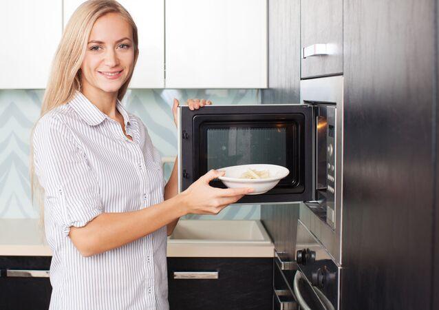 Kobieta wstawia talerz do mikrofali