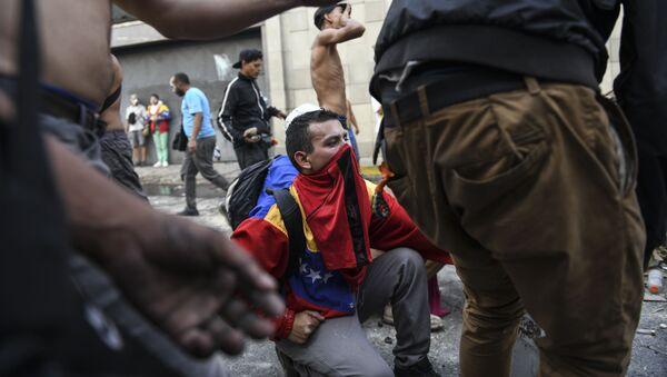 Protestujący w czasie starcia z Gwardią Narodową Wenezueli w Caracas - Sputnik Polska