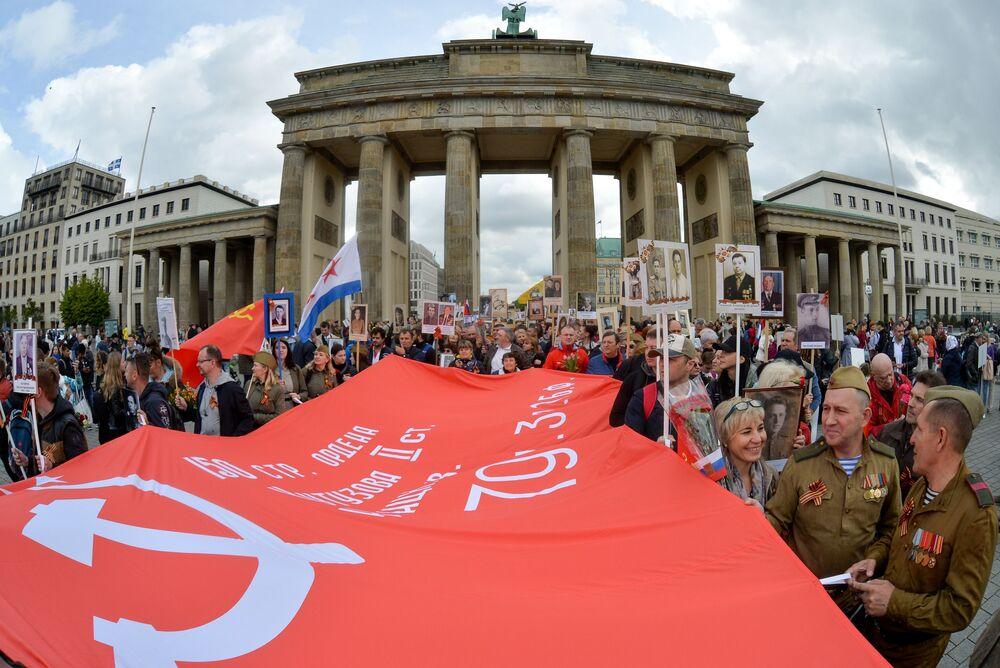 """Uczestnicy akcji """"Nieśmiertelny pułk"""" przy Bramie Brandenburskiej w Berlinie."""
