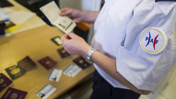 Oficer francuskiej policji przegląda fałszywe paszporty - Sputnik Polska