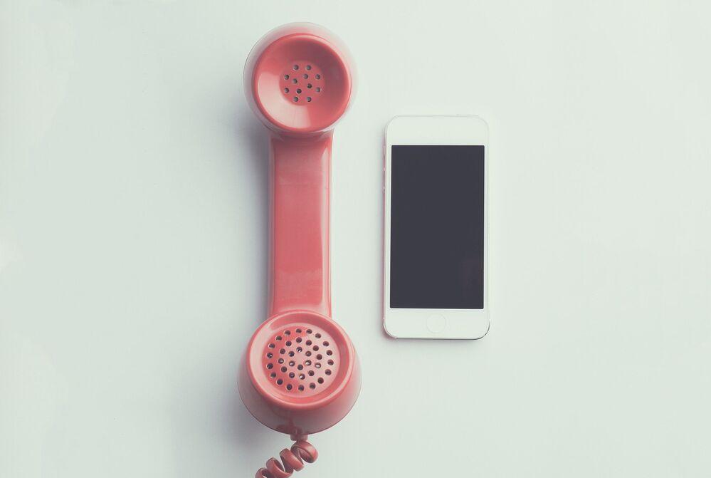 Słuchawka starego telefonu obok nowoczesnego telefonu komórkowego.