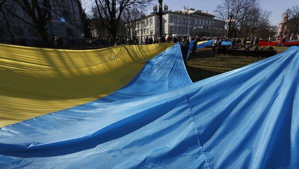Ludzie trzymający ukraińską flagę w czasie świętowania Dnia Niepodległości w Wilnie - Sputnik Polska
