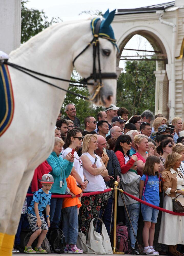 """Widzowie podczas ceremonii rozejścia się pieszej i konnej straży z udziałem młodych jeźdźców """"Kremlowskiej Szkoły Jeździeckiej"""" na Placu Katedralnym Moskiewskiego Kremla."""