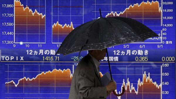 Mężczyzna przechodzi obok tablicy z notowaniami indeksu giełdowego Japonii - Sputnik Polska