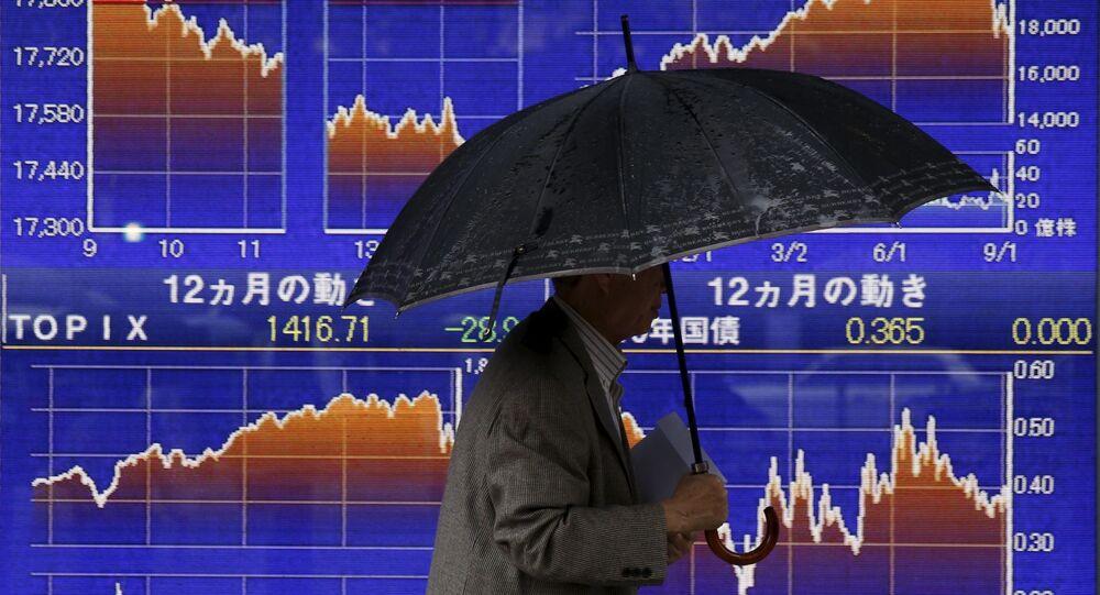Mężczyzna przechodzi obok tablicy z notowaniami indeksu giełdowego Japonii