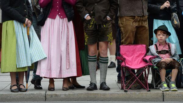 Chłopczyk w tradycyjnym stroju bawarskim czeka na rozpoczęcie parady strojów podczas festiwalu piwa Oktoberfest w Monachium - Sputnik Polska