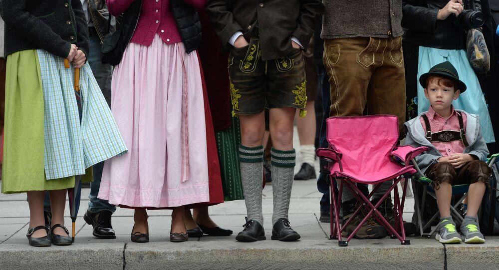 Chłopczyk w tradycyjnym stroju bawarskim czeka na rozpoczęcie parady strojów podczas festiwalu piwa Oktoberfest w Monachium