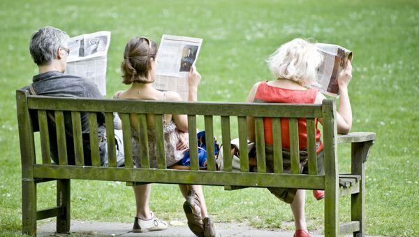 Ludzie czytający prasę na ławce - Sputnik Polska