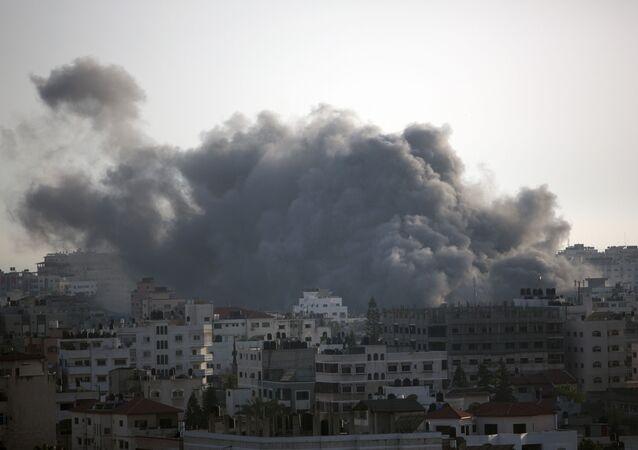 Czarny dym spowodowany przez izraelski nalot unosi się nad domami w mieście Gaza